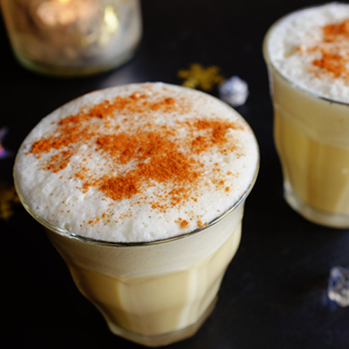 Eggnogg in a glass with a candle